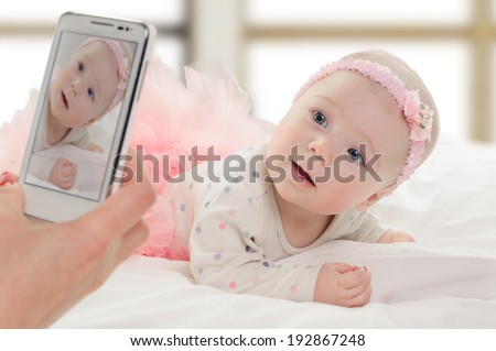 taking portrait of six month old baby girl in pink dress. on window background - stock photo