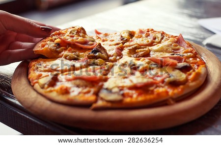 Taking slice of tasty pizza close-up. Selective focus. - stock photo