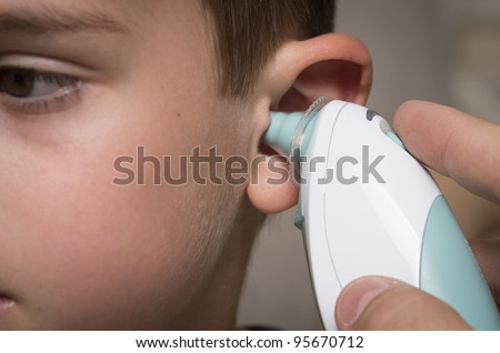 Taking temperature using in ear thermometer - stock photo
