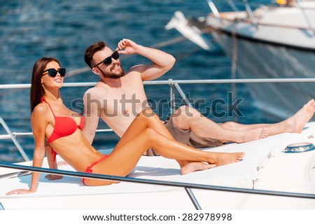Taking their summer vacation. Smiling young couple sunbathing while sitting on the deck of yacht  - stock photo