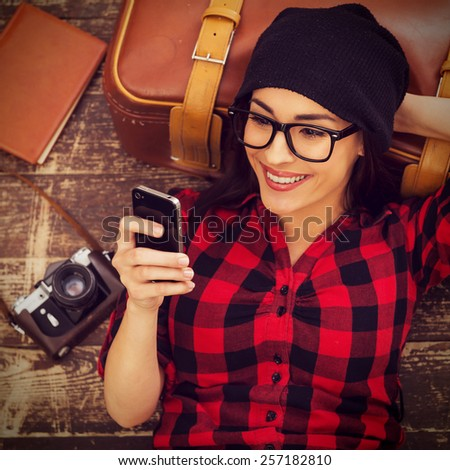 Taking time for a break. Top view of beautiful young woman in headwear lying on the floor holding mobile phone and smiling - stock photo