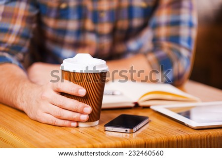 Taking time for coffee break. Close-up of man holding coffee cup while sitting at the desk with note pad and digital tablet laying on it - stock photo