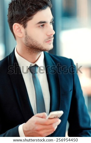 Taking time for coffee break. Confident business man in suit drinking coffee and typing a message on mobile phone while sitting in restaurant - stock photo