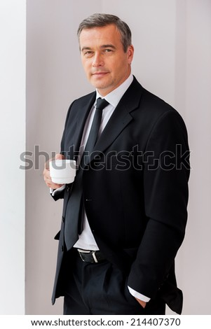 Taking time for coffee break. Confident mature man in formalwear holding coffee cup and looking at camera while standing near the window - stock photo