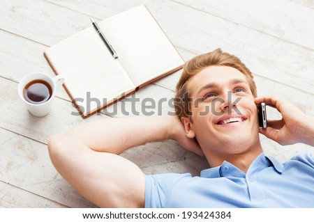 Taking time to relax. Top view of handsome young man talking on the mobile phone and smiling while lying on the floor at his apartment - stock photo