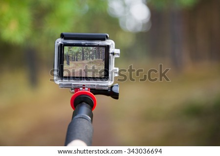 taking video with action camera on handheld stick - stock photo