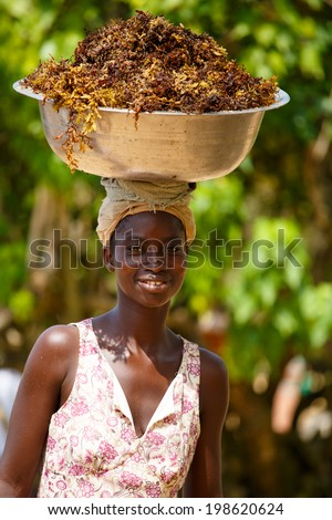 TAKORADI, GHANA �¢?? MARCH 22: Unidentified african woman carry sea weeds on her head on March 22, 2014 in Takoradi, Ghana. Carrying things on head is general skill of African girls and women. - stock photo