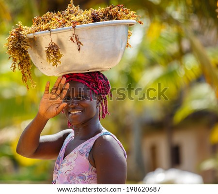 TAKORADI, GHANA - MARCH 22: Unidentified african woman carry sea weeds on her head on March 22, 2014 in Takoradi, Ghana. Carrying things on head is general skill of African girls and women.