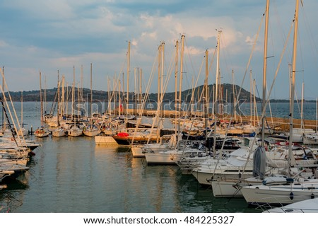 TALAMONE, TUSCANY - SEPTEMBER 10, 2016 -  The small port of the town of Talamone at sunset with moored boats.