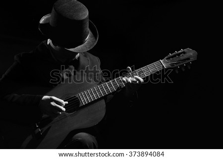 Talent and virtuosity. Black and white top view image of man playing acoustic guitar