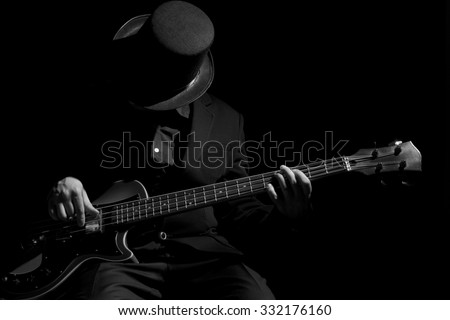Talent and virtuosity. Black and white top view image of man playing bass guitar - stock photo