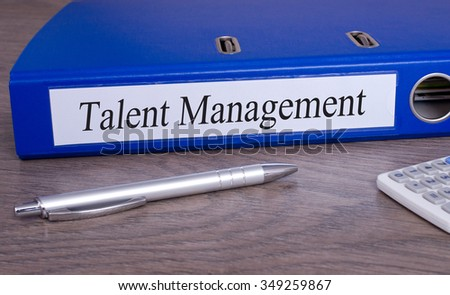 Talent Management - blue binder with text on desk in the office