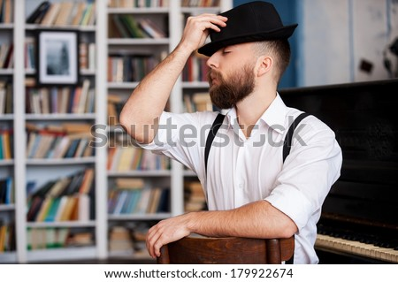 Talented and creative. Portrait of handsome young bearded men sitting in front of his piano with closed eyes - stock photo