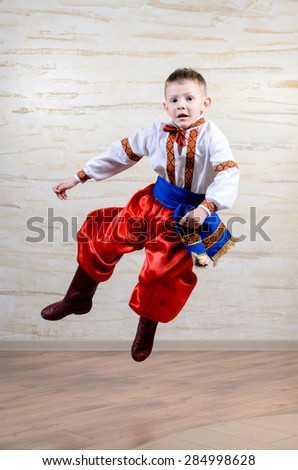 Talented child wearing Eastern European folk costume with embroidered white shirt and belt, red pants and boots, in a mid-air leap while performing a traditional dance - stock photo