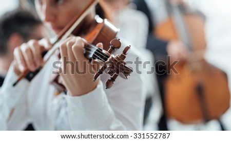 Talented female violinist playing her violin with classical music symphony orchestra on background
