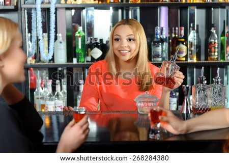 Talk at the bar. Smiling attractive female bartender talking to the guests holding a bottle with red drink