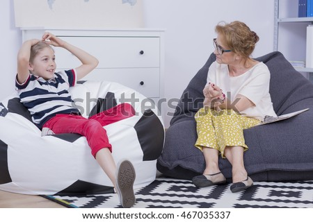 Talk between mature woman and young boy sitting on bean bag chairs