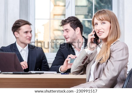 Talk on the phone. Businesswoman sitting at a table and talking on cell phone while her colleague businessmen talking in the background sitting at table
