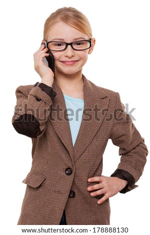 Talking about business. Cheerful little girl in formalwear talking on the mobile phone and holding hand on hip while standing isolated on white - stock photo