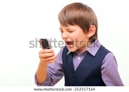 Talking about business. Closeup of frustrated little boy in formalwear talking over the mobile phone and shouting while standing isolated on white background