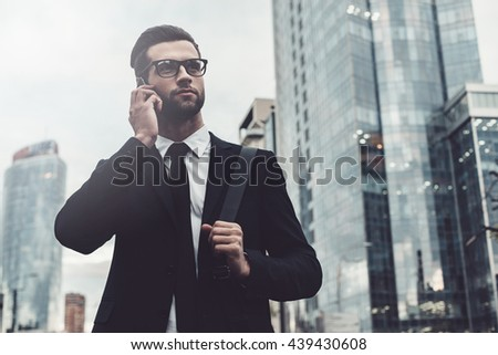 Talking about business. Confident young man in full suit talking on the mobile phone and looking away while standing outdoors with cityscape in the background - stock photo