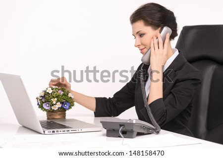 Talking at phone. Confident middle-aged businesswoman sitting at her working place talking at phone - stock photo