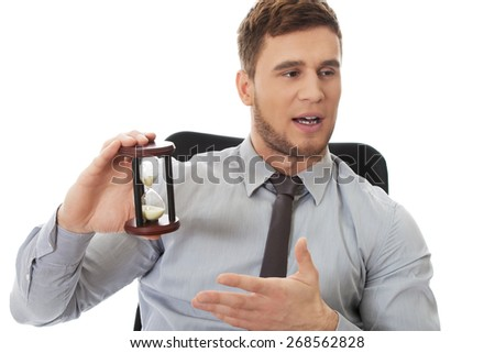 Talking businessman holding hourglass in the office. - stock photo