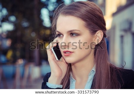 Talking. Closeup portrait headshot young pretty serious business woman in formal wear black suit white shirt holding cellphone discussing on mobile making appointments by phone while walking a street - stock photo