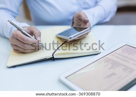 Talking notes on a notebook, tablet computer, smartphone, close-up - stock photo