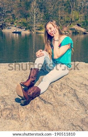 Talking on Phone. Dressing in a blue sleeveless top, fashionable jeans, brown boots, a blonde teenage girl is sitting on rocks by a lake, talking on her cell phone. Instagram Nashville effect.  - stock photo