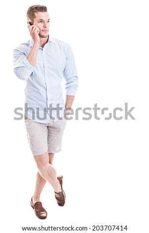 Talking on the phone - Full length portrait of a young man standing in front of white background and chatting on smartphone - stock photo