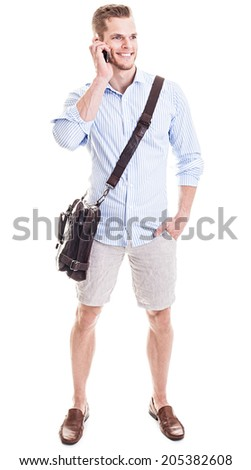 Talking on the phone - Full length portrait of a young man standing in front of white background and chatting on mobile phone - stock photo