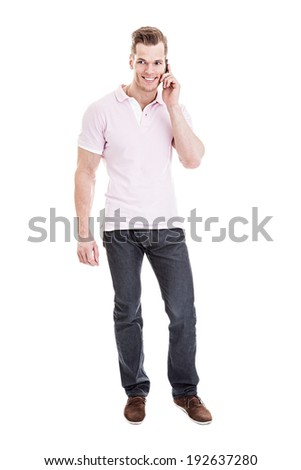 Talking on the phone - Full length portrait of a young man taking a selfie with his smart phone, isolated on white background - stock photo
