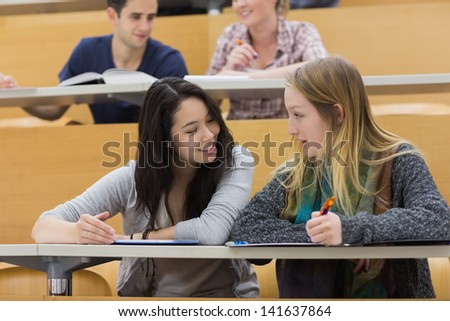 Talking students sitting in a lecture hall and studying while writing and using a tabet computer - stock photo