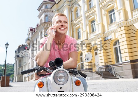 Talking to you. Youthful attractive man sitting on scooter and talking per mobile phone. - stock photo