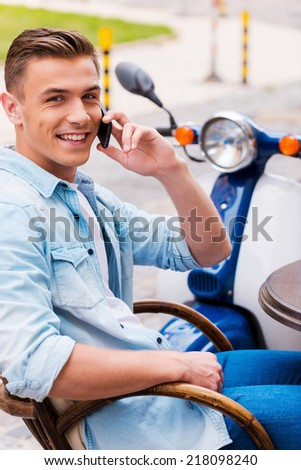 Talking with friend. Relaxed young man talking on the mobile phone and smiling while sitting in sidewalk cafe with scooter in the background - stock photo