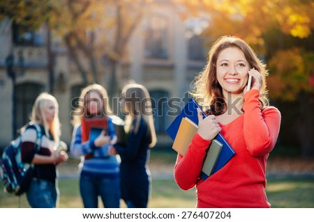 Talking with friends. Handsome young woman talking on the mobile phone and smiling while standing against university building with his friends chatting in the background - stock photo