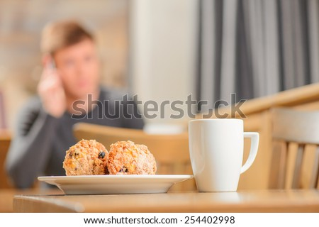 Talking with friends. Selective focus image of a cup of coffee with cookies with a confident young man talking on the mobile phone sitting in city cafe on the background - stock photo