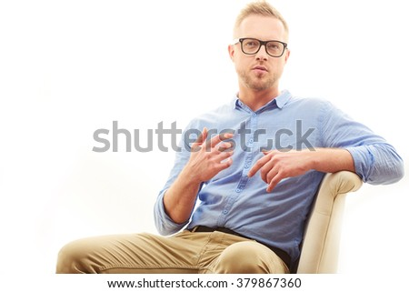 Talking young man. Portrait of handsome young man in casual blue shirt and dioptrical glasses sitting in comfortable pose isolated on white background - stock photo