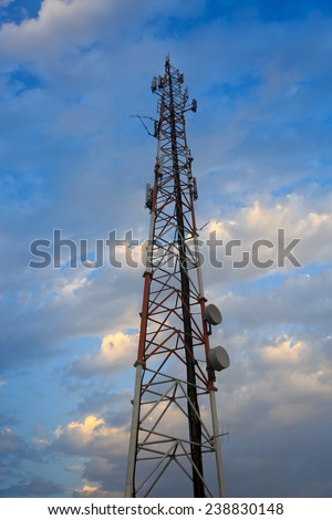 Tall antenna mast standing under clouds - stock photo