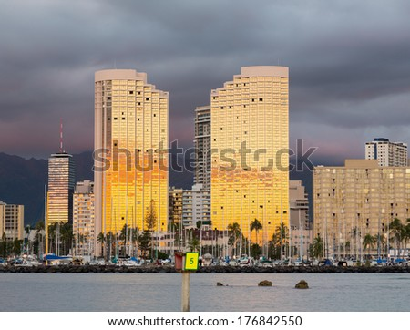 Tall apartment blocks in Honolulu reflect the setting sun in their mirrored windows as the sunset illuminates the clouds behind - stock photo