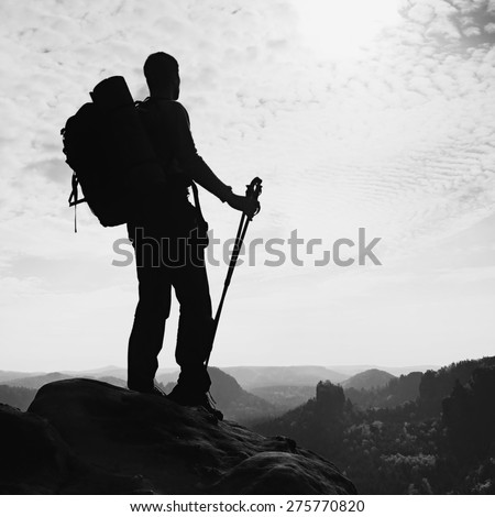 Tall backpacker with poles in hand. Sunny spring daybreak in rocky mountains. Hiker with big backpack stand on rocky view point above misty valley. Black and white photo. - stock photo