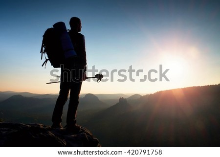 Tall backpacker with poles in hand. Sunny spring daybreak in rocky mountains. Hiker with big backpack stand on rocky view point above misty valley.  - stock photo