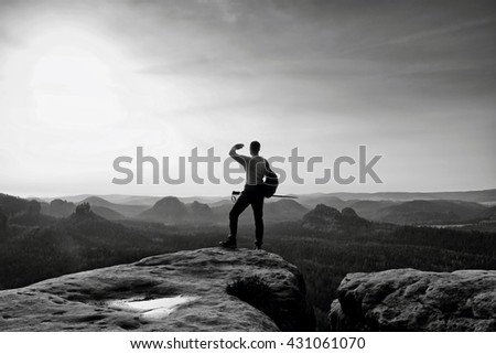 Tall backpacker with poles in hand. Sunny spring daybreak in rocky mountains. Hiker with big backpack stand on rocky view point above misty valley. Black and white photo - stock photo