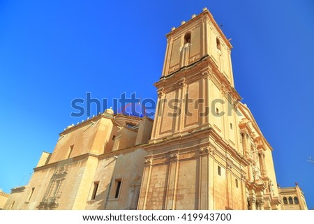 Tall belfry dominates the building of Santa Maria Basilica in Elche, Alicante, Spain - stock photo