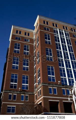 Tall brick building with blue tinted windows covered on two sides with clear blue sky