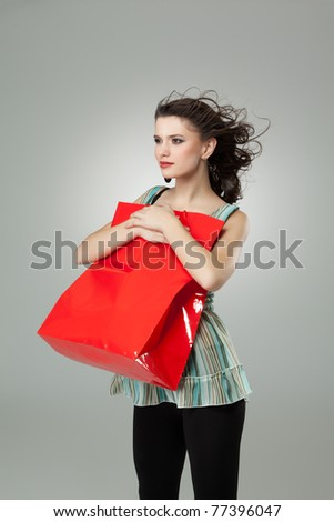 tall brunette woman holding red shopping bag - stock photo