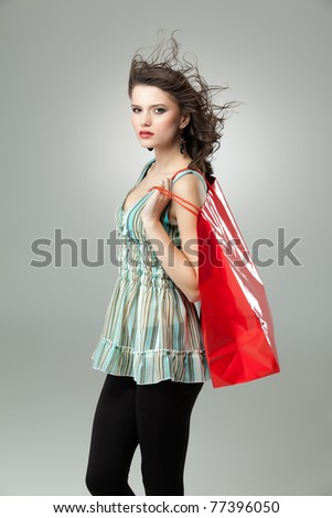 tall brunette woman holding shopping red bag