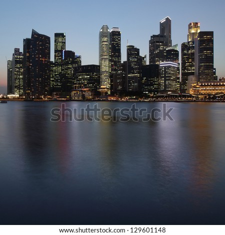 Tall buildings of a city reflected in a water at twilight - stock photo