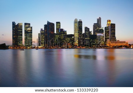 Tall buildings reflected in a water at twilight